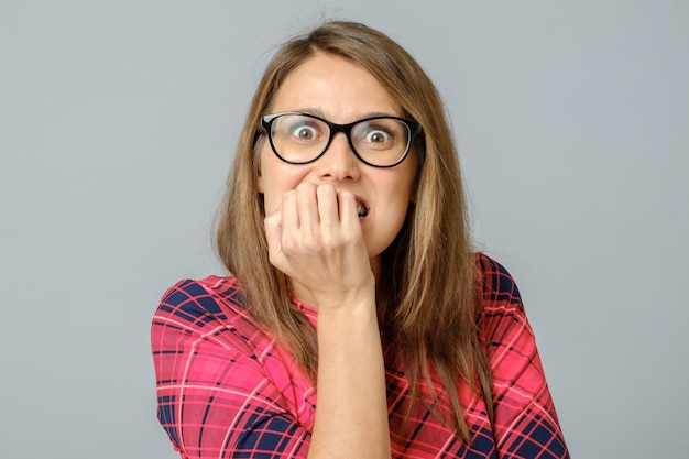Retrato de mulher preocupada com medo atraente, roer unhas