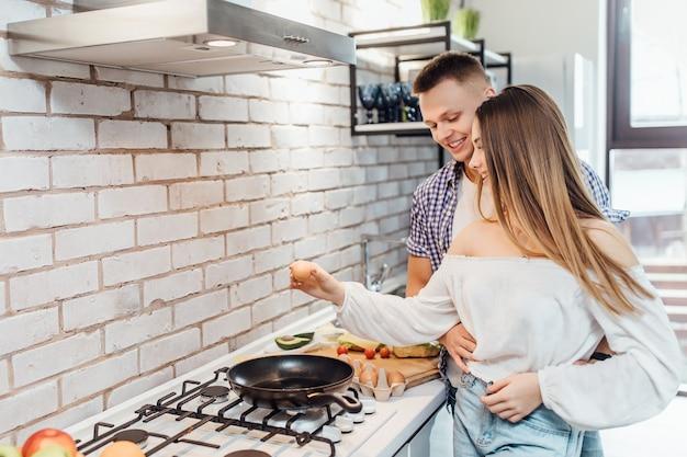 Retrato de mulher quebrando um ovo sobre uma frigideira no fogão. fêmea, preparando o café da manhã com o homem em pé.