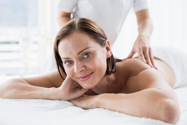 Retrato de mulher recebendo massagem nas costas do massagista