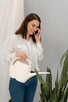 Retrato de mulher regando planta enquanto fala no celular