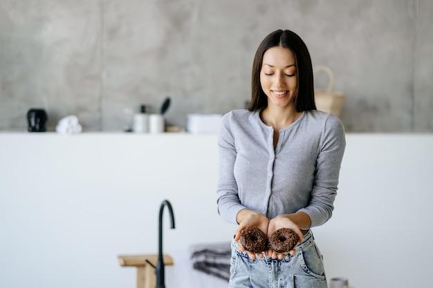 Retrato de mulher regozijando-se segurando uma rosquinha saborosa em casa. conceito de alimentos pouco saudáveis.