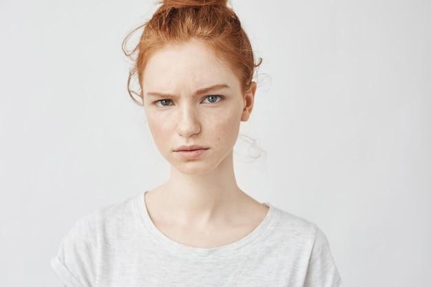 Retrato de mulher ruiva chateada.