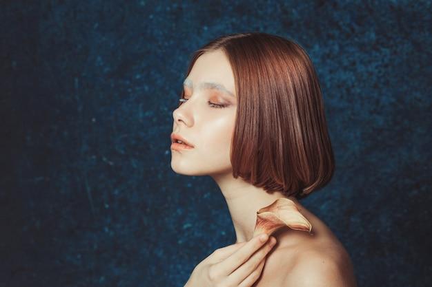 Retrato de mulher ruiva com lírio de calla no ombro