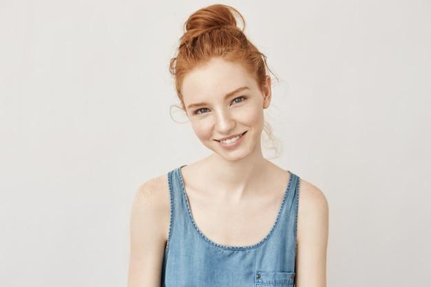 Retrato de mulher ruiva feliz com sardas sorrindo sinceramente, não tem medo de uv e queimaduras solares.