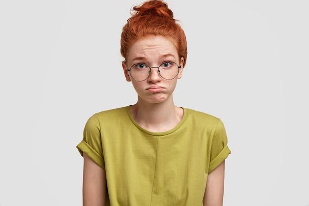 Retrato de mulher ruiva franze o lábio inferior em descontentamento, sente-se insultado ao ouvir comentários negativos e usa uma camiseta casual brilhante