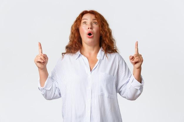 Retrato de mulher ruiva impressionada e ofegante, maravilhada, boca aberta fascinada, dizendo uau, olhando e apontando o dedo para uma super oferta, mostrando um banner com propaganda.