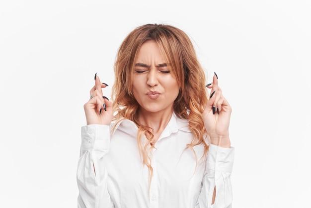 Retrato de mulher ruiva jovem em roupas brancas casuais, cruzando os dedos, mordendo o lábio inferior, sentindo-se nervoso antes de um evento importante.