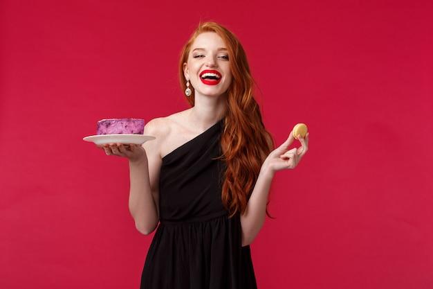 Retrato de mulher ruiva linda despreocupada de vestido preto, rindo sobre piada engraçada na festa, segurando o bolo no prato e biscoito, comendo sobremesas deliciosas, aproveitando a festa de aniversário perfeita