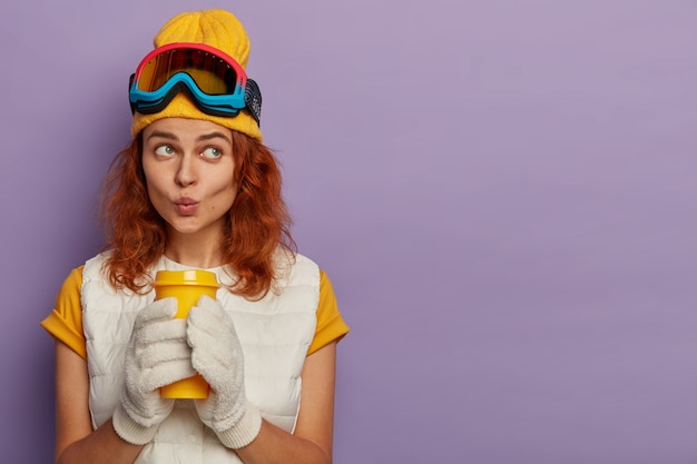 Retrato de mulher ruiva pensativa, vestida com roupas casuais, mantém os lábios arredondados, gosta de bebidas aromáticas e óculos protetores em poses de cabeça interiores.