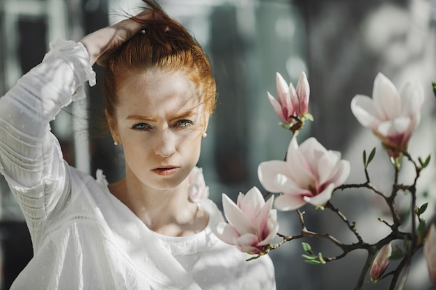 Retrato de mulher ruiva perto de um galho de magnólia
