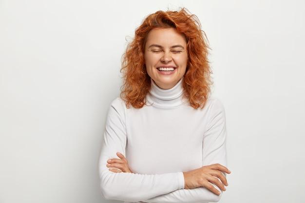 Retrato de mulher ruiva radiante ri de uma piada engraçada, mantém os braços cruzados, se diverte dentro de casa, mantém os olhos fechados, vestida com um macacão casual, isolado no branco. conceito de emoções e sentimentos.