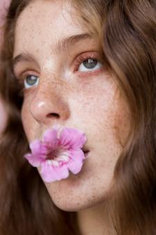 Retrato de mulher sardenta com uma flor na boca, close-up