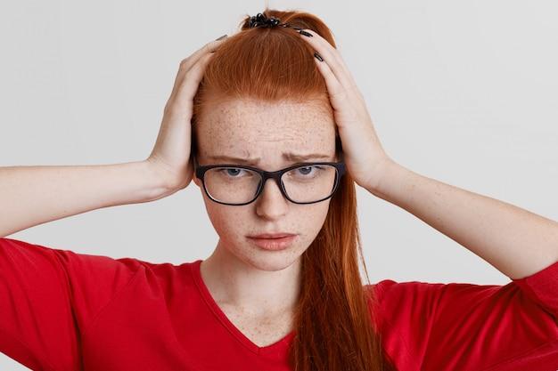 Retrato de mulher sardenta emocional frustrada mantém as mãos na cabeça, usa óculos quadrados, tem dor de cabeça