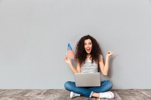 Retrato de mulher satisfeita com sorriso bonito sentado em pose de lótus com computador prateado nas pernas segurando a bandeira americana na mão sobre parede cinza