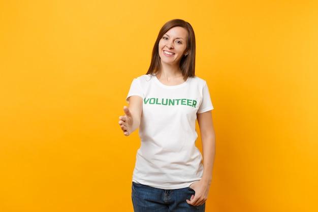 Retrato de mulher satisfeita sorridente feliz em camiseta branca com voluntário de título verde de inscrição escrita isolado em fundo amarelo. ajuda de assistência gratuita voluntária, conceito de trabalho de graça de caridade.