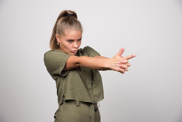 Retrato de mulher segurando a mão dela como uma arma.
