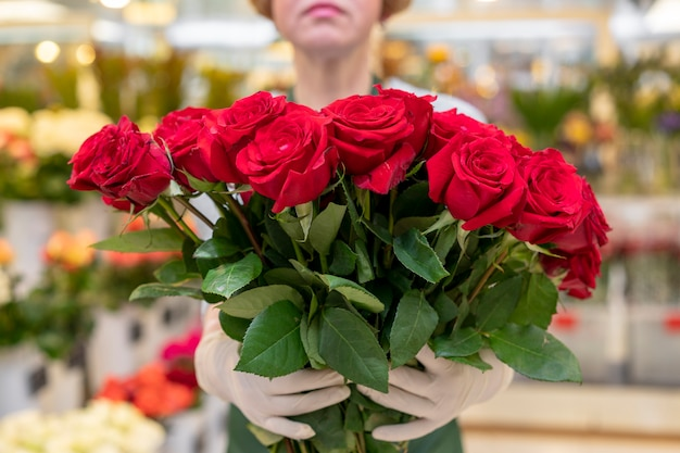 Retrato de mulher segurando coleção de rosas vermelhas