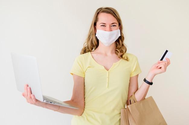 Retrato de mulher segurando laptop e sacola de compras