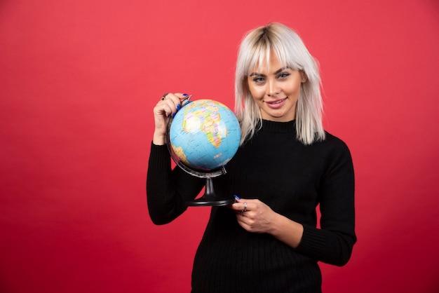 Retrato de mulher segurando um globo terrestre em uma parede vermelha.