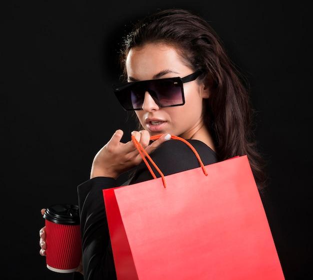 Retrato de mulher segurando uma grande sacola de compras vermelha