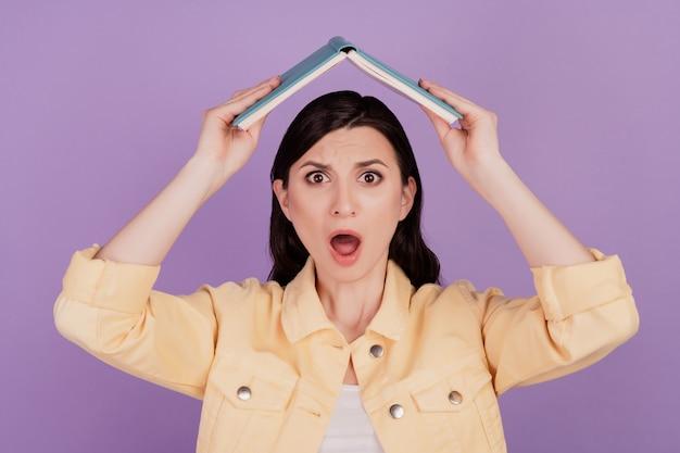 Retrato de mulher sem palavras segurando livro levantando as mãos figura do telhado boca aberta sobre fundo roxo