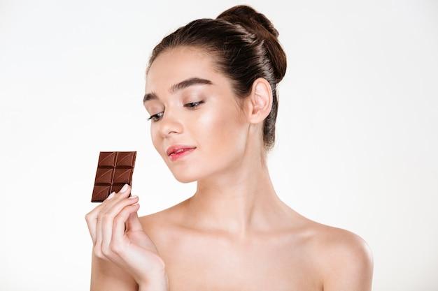 Retrato de mulher seminua atraente, com cabelos escuros, desfrutando de doces comendo uma barra de chocolate ao leite