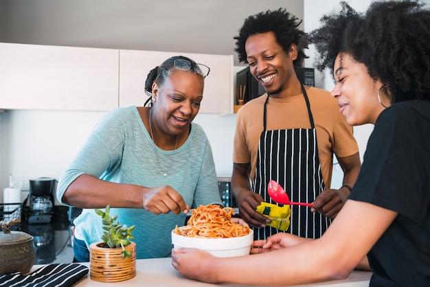 Retrato de mulher sênior ajudando filha e genro a cozinhar em casa