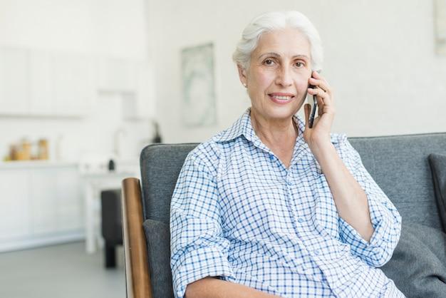 Retrato, de, mulher sênior, conversa telefone móvel, casa