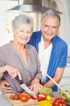 Retrato, de, mulher sênior, corte, enquanto, seu, marido, abraçando ela, em, cozinha