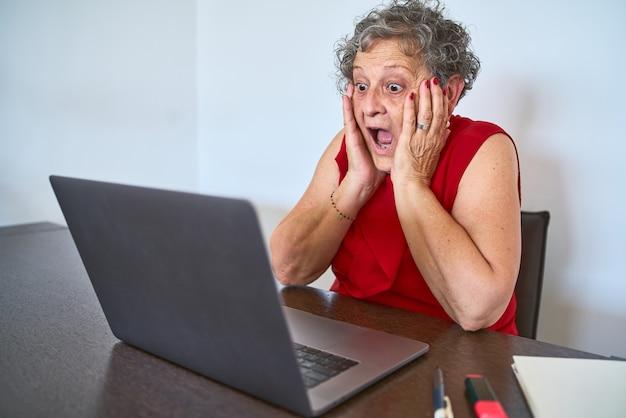 Retrato de mulher sênior em choque olhando para o computador de mãos dadas ao lado do rosto