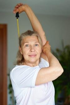 Retrato de mulher sênior exercício para esportes em casa. aptidão doméstica.