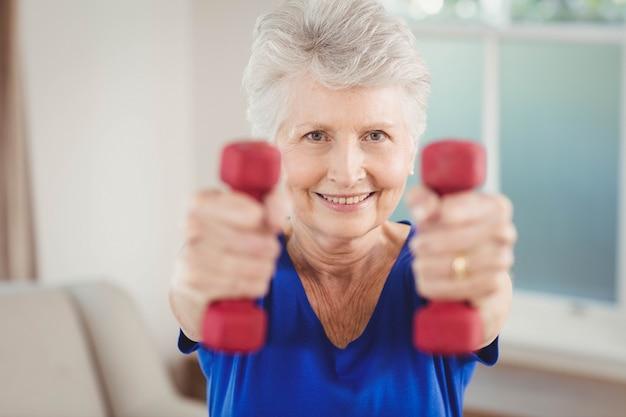 Retrato, de, mulher sênior, exercitar, com, dumbbells, casa