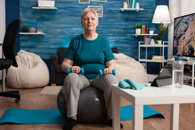 Retrato de mulher sênior olhando para a câmera enquanto está sentado na bola suíça, treinando músculos corporais, segurando halteres de fitness durante o treino de cardio-ginásio