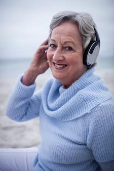 Retrato de mulher sênior ouvindo música em fones de ouvido