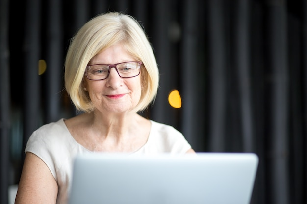 Retrato de mulher sênior positiva usando laptop
