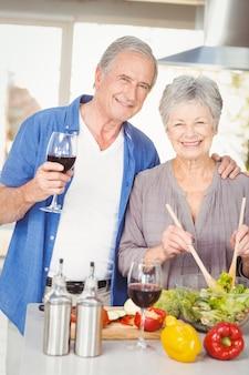 Retrato de mulher sênior preparando uma salada enquanto seu marido está de pé com vinho tinto