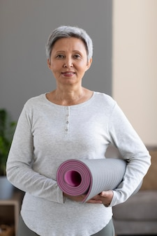Retrato de mulher sênior segurando um tapete de ioga