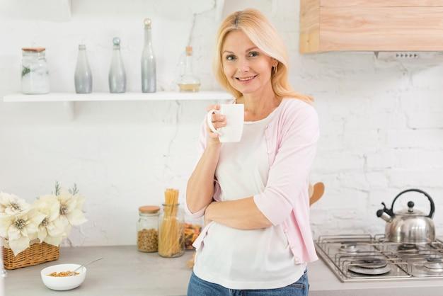 Retrato, de, mulher sênior, segurando uma xícara café
