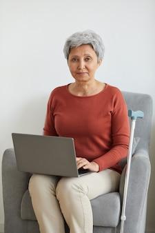 Retrato de mulher sênior sentada no sofá sorrindo enquanto usa o laptop em casa