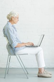 Retrato, de, mulher sênior, sentando, ligado, cadeira, usando computador portátil