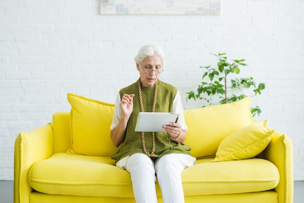 Retrato, de, mulher sênior, sentando, ligado, sofá amarelo, olhar, tablete digital