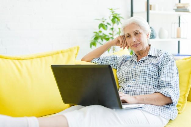Retrato, de, mulher sênior, sentando, ligado, sofá, browsing, laptop