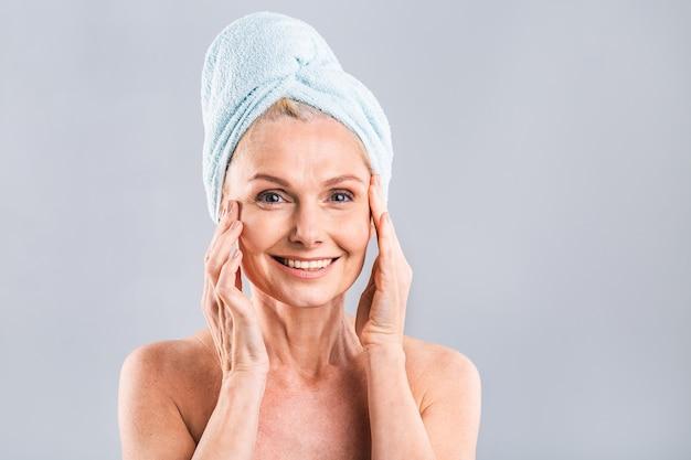 Retrato de mulher sênior sorridente, sentindo a pele macia com a mão após o banho de spa.