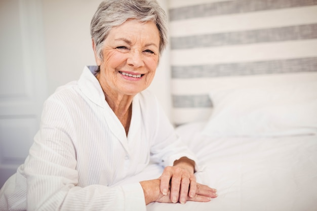 Retrato, de, mulher sênior, sorrindo, enquanto, sentar-se cama