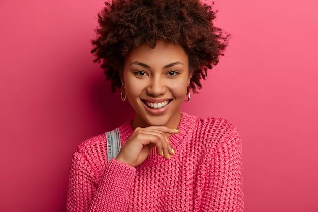 Retrato de mulher sensual e cacheada sorri agradavelmente, segura o queixo, expressa emoções positivas, continua sorrindo, mostra dentes brancos, usa suéter de malha rosa, tem rosto bonito, pele saudável, cabelo cacheado