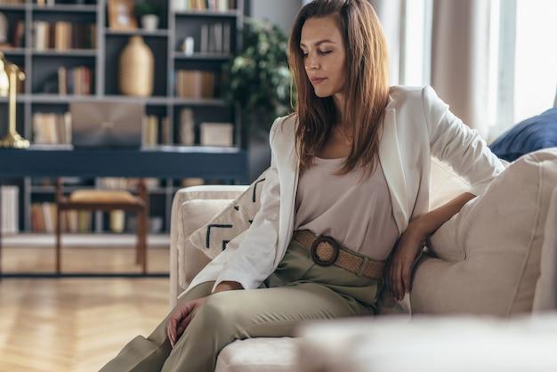 Retrato de mulher sentada no sofá da sala.