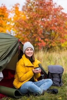Retrato de mulher sentada perto de uma tenda verde e bebendo chá ou café na floresta de outono