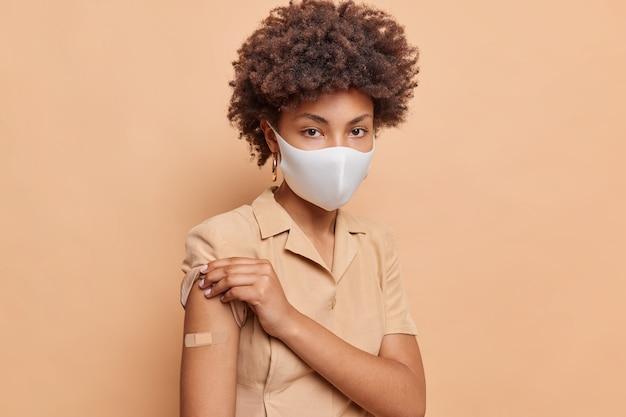 Retrato de mulher séria de cabelo encaracolado arregaça a manga do vestido mostra local de vacinação usa bandagem adesiva no braço recebe vacina antivírus para vida segura usa máscara protetora facial poses indoor