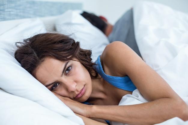 Retrato de mulher séria, deitada na cama