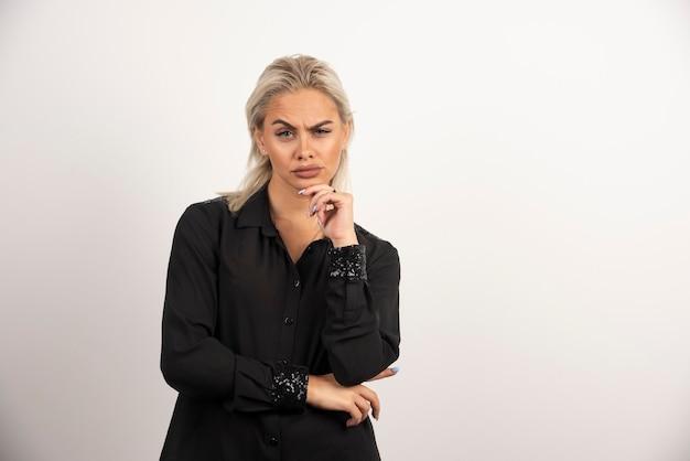 Retrato de mulher séria em camisa preta, posando em fundo branco. foto de alta qualidade